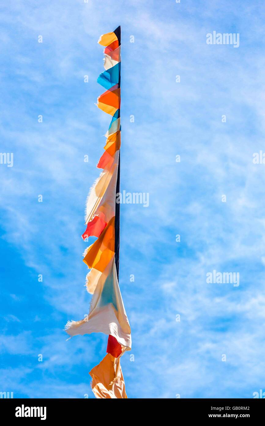 a flagpole with flags and pennants rising up into a blue sky - Stock Image