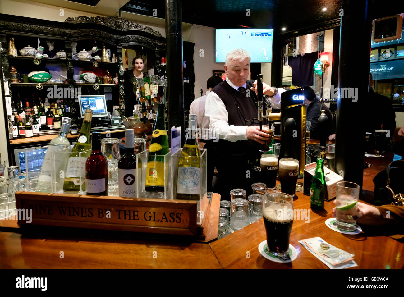 Bartender pouring a pint of beer at The Old Stand pub in Dublin, Republic of Ireland, Europe - Stock Image