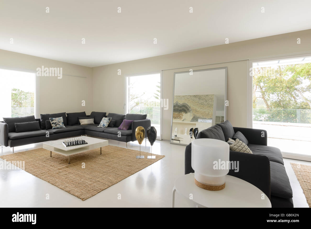 Modern living room with big sofas and luminous large windows - Stock Image