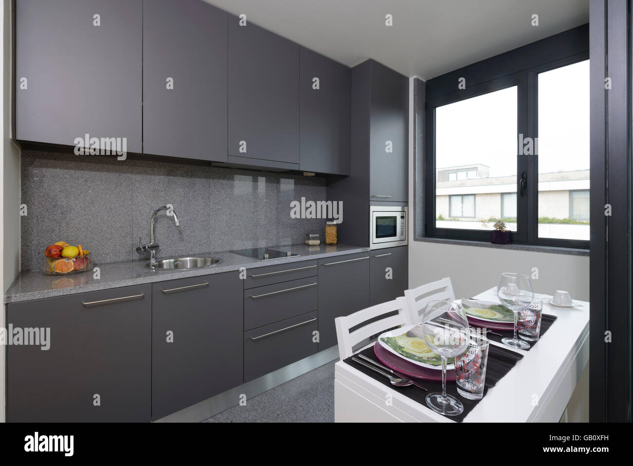 Small modern grey kitchen with dining table - Stock Image