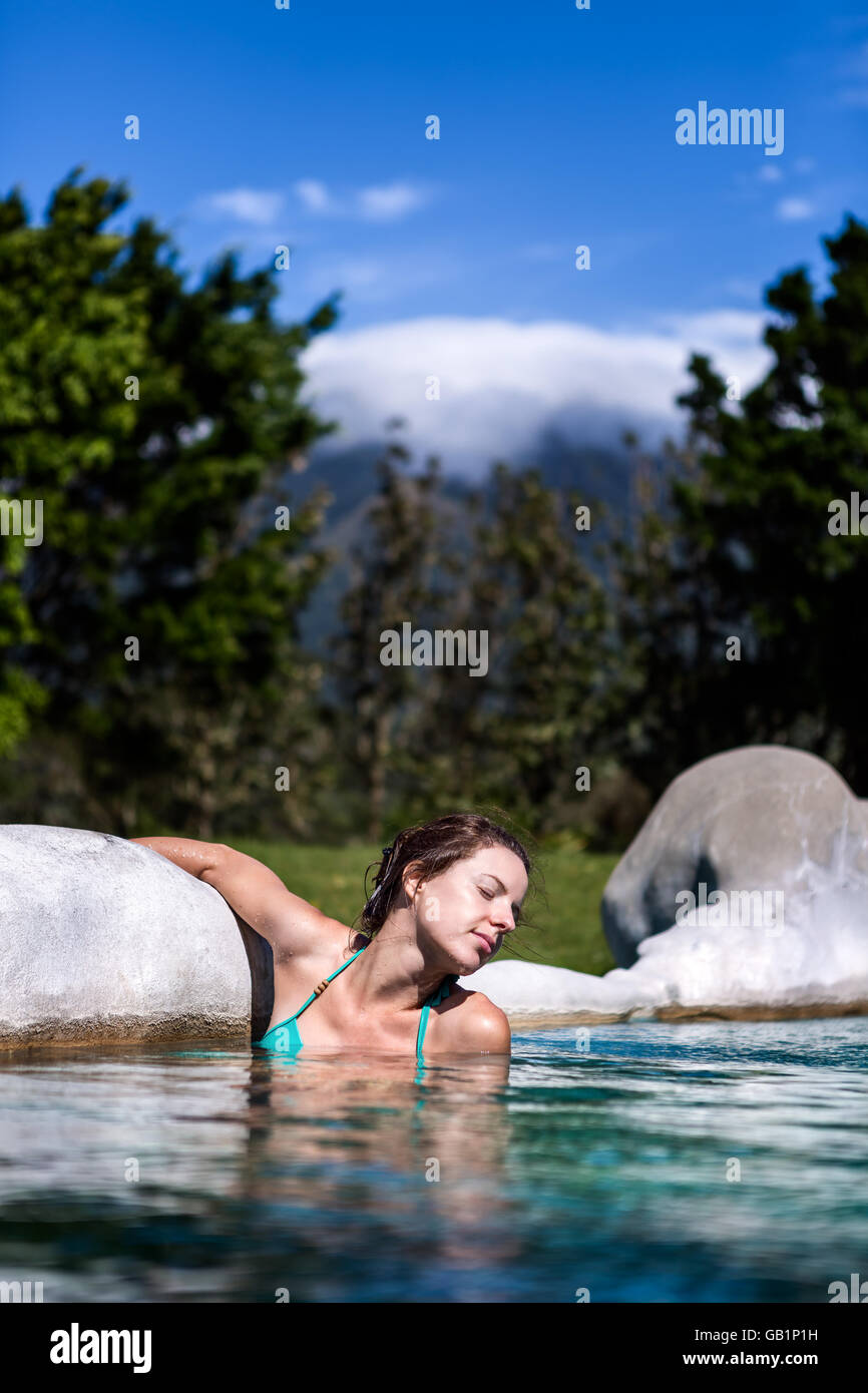 Beautiful women relaxing in the hot springs with the Volcano Miravalles in the background, Costa Rica, Guanacaste. - Stock Image