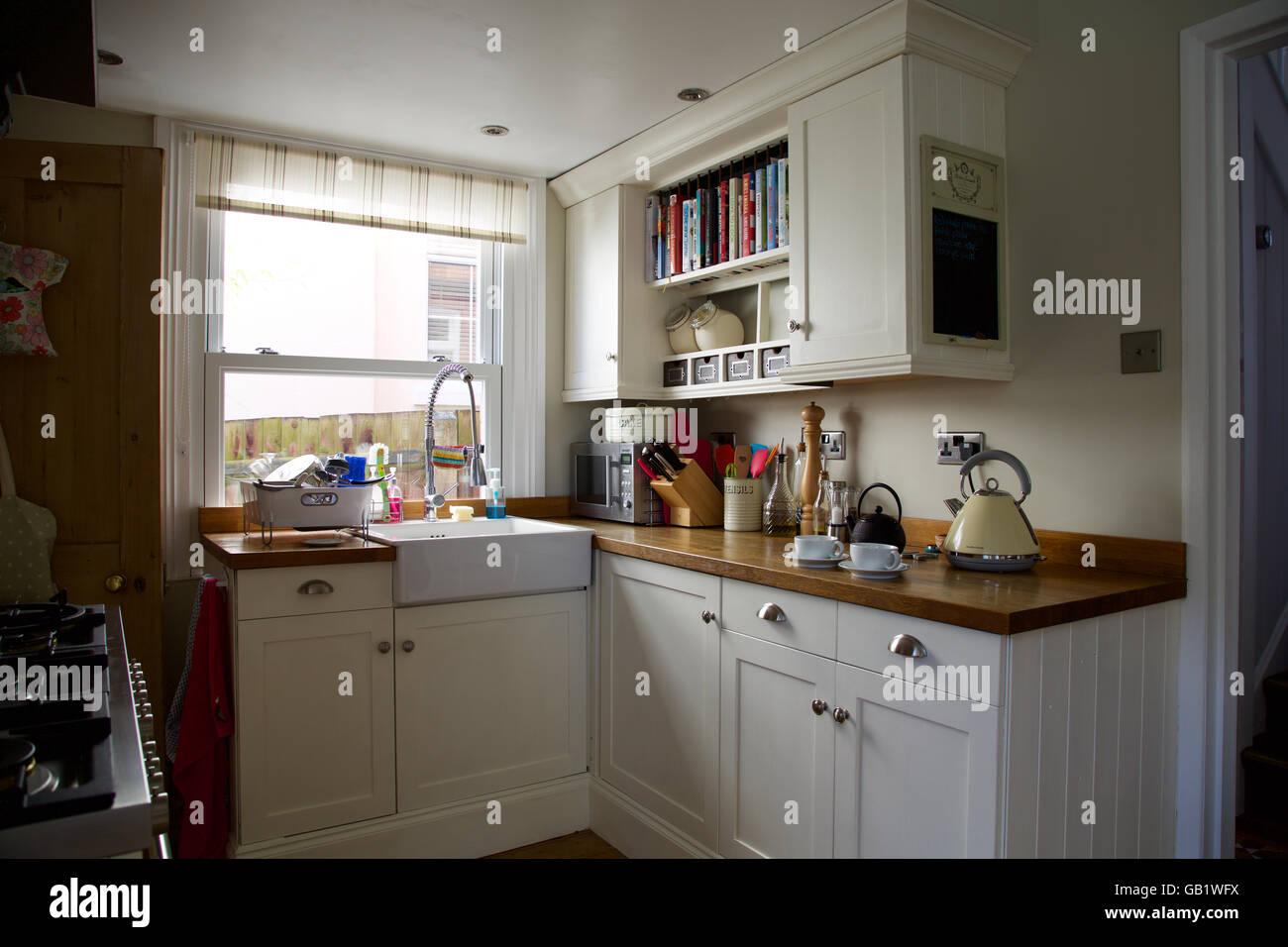 Victorian kitchen corner with window in real family home kettle tea cup pot sink cream cupboards worktop breakfast - Stock Image