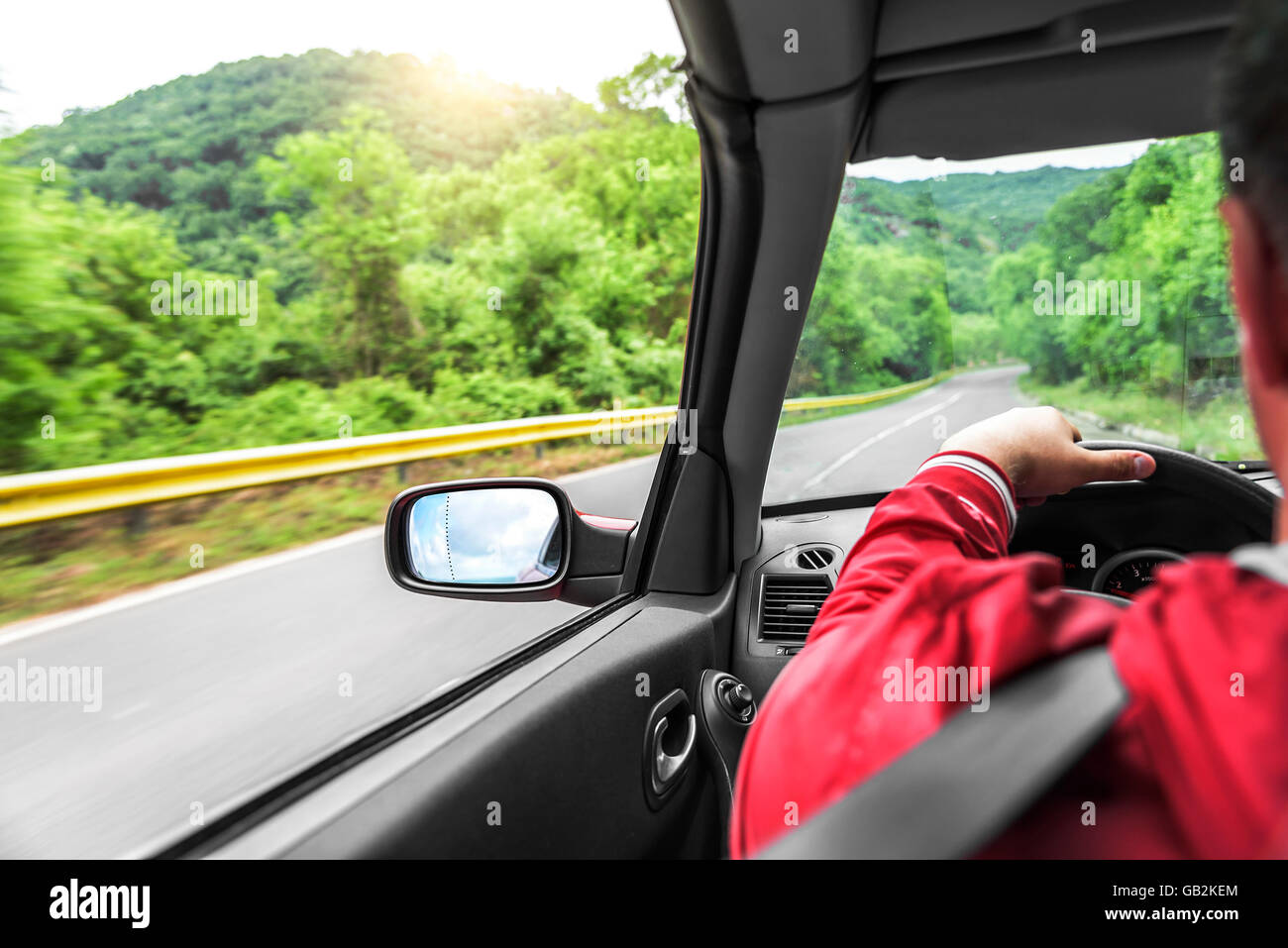 Male driver drives a convertible car on the country road. The view from the cabin, rear view, inside. - Stock Image