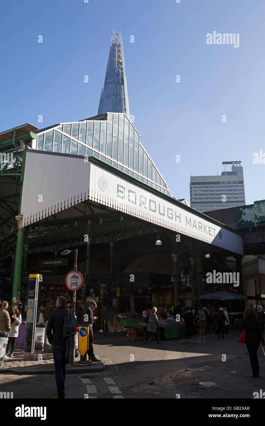 The Shard towers over Borough Market in London, England. Stalls selling food and drink operate from the market. - Stock Image
