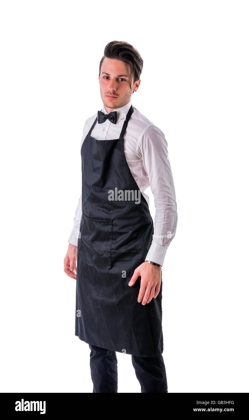 Young chef or waiter posing, welcoming guests with a smile, wearing black apron and white shirt isolated on white - Stock Image