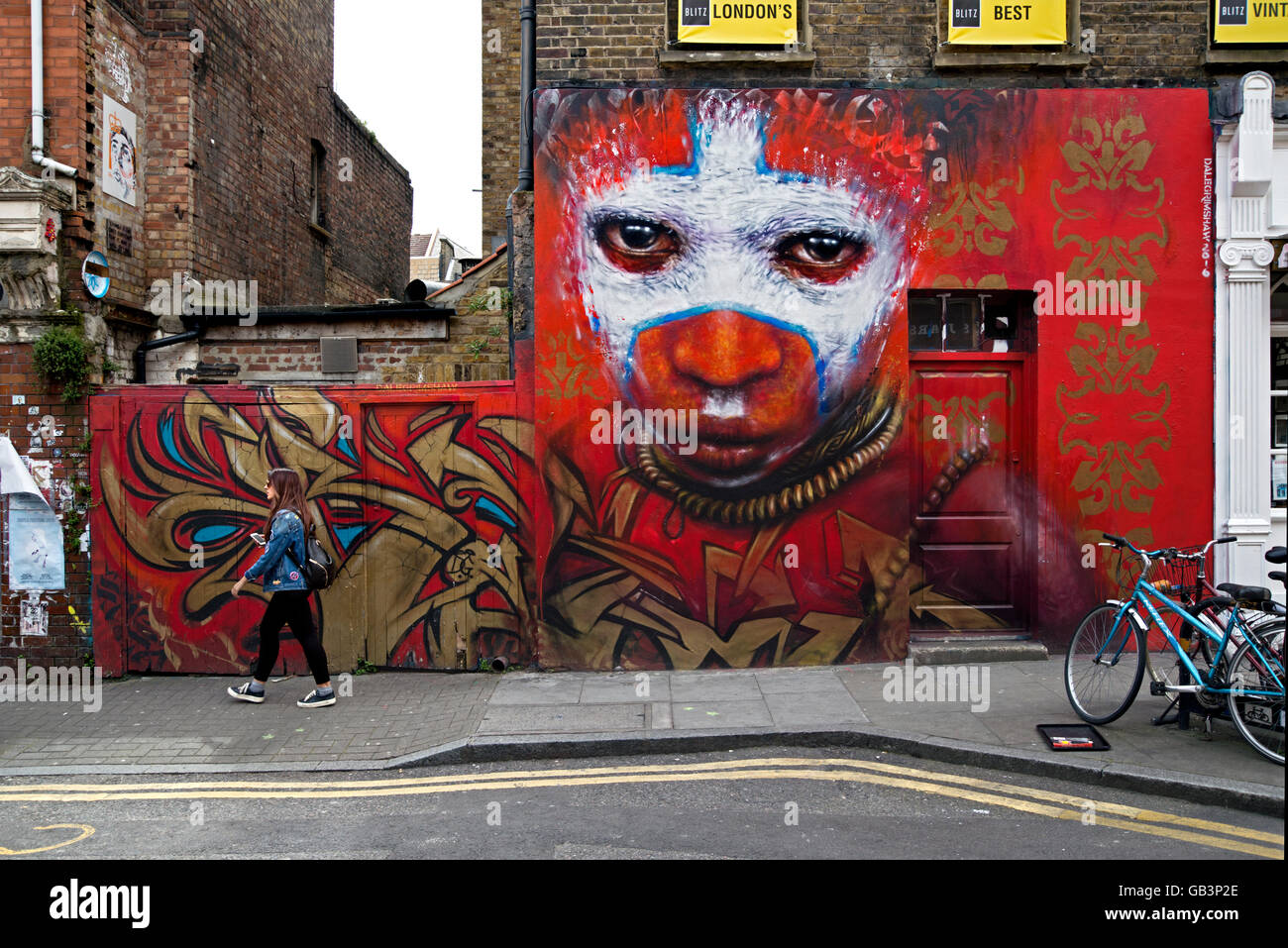 A young woman walks by a piece of street art by Dale Grimshaw in Hanbury Street, just off Brick Lane, London. Stock Photo