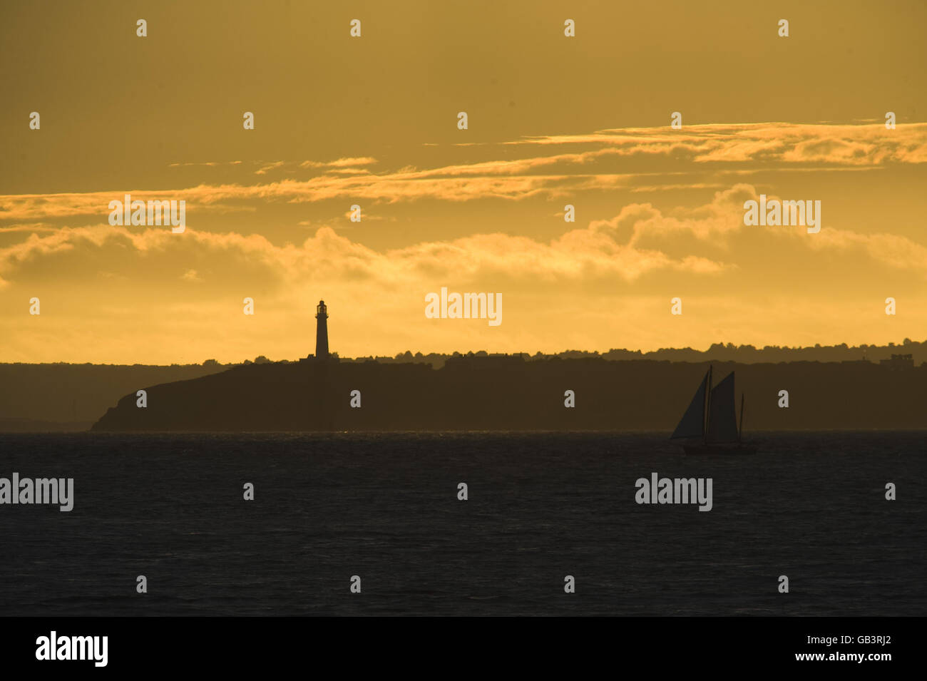 The sun casts a golden glow as it sets over Flatholme lighthouse situated in the Bristol Channel between Weston-super-Mare and Cardiff bringing some welcomed relief after the recent poor weather that has covered much of the UK. Stock Photo