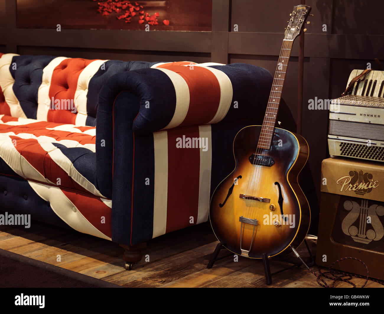 Vintage acoustic Gibson guitar on a stand at a sofa with Union Jack pattern - Stock Image