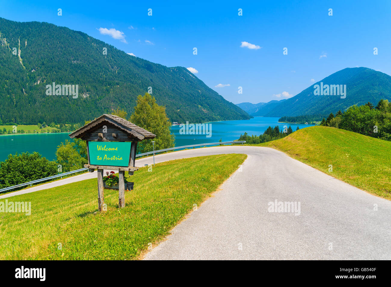 View of weissensee lake with sign along a road with words welcome view of weissensee lake with sign along a road with words welcome to austria greeting painted on board austria m4hsunfo