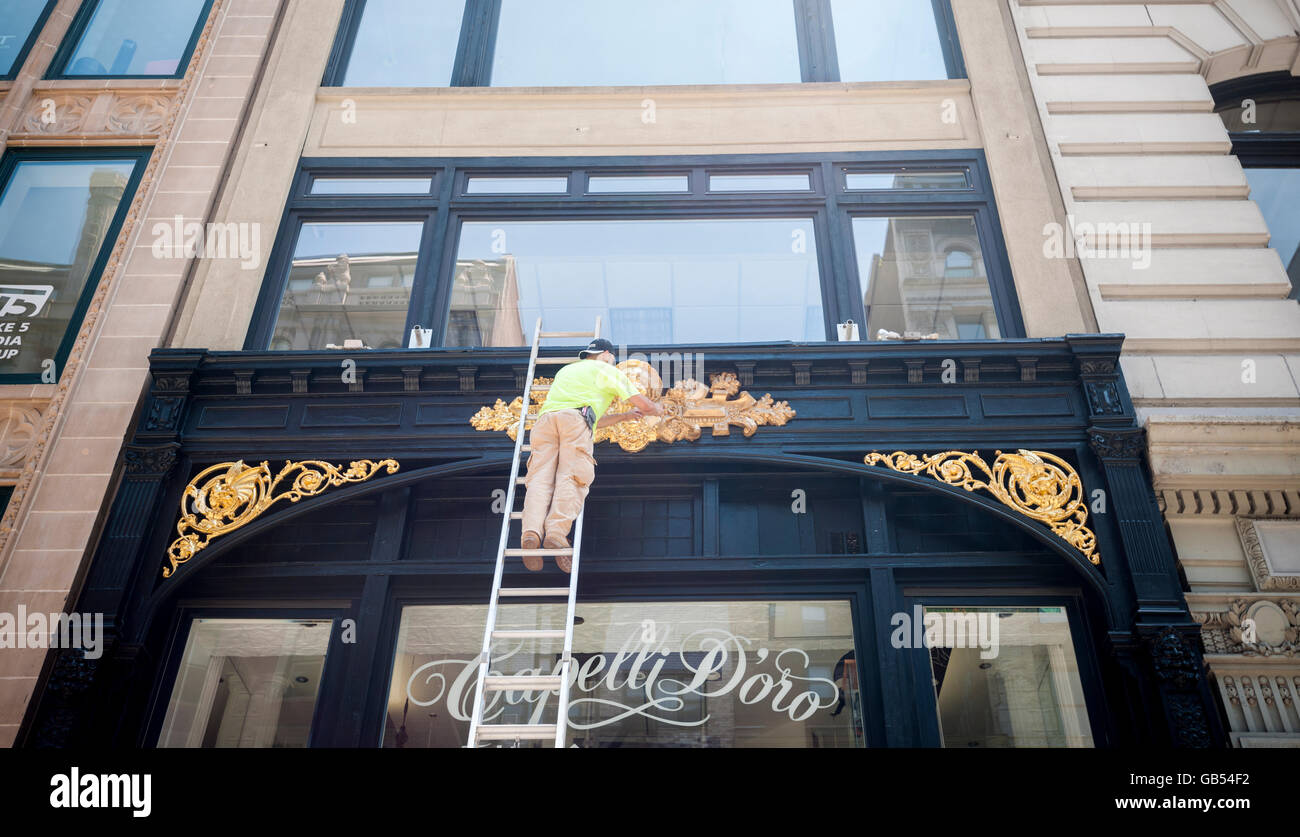 A worker applies gilding to the facade of a building in New York on Monday, July 4, 2016. (© Richard B. Levine) - Stock Image