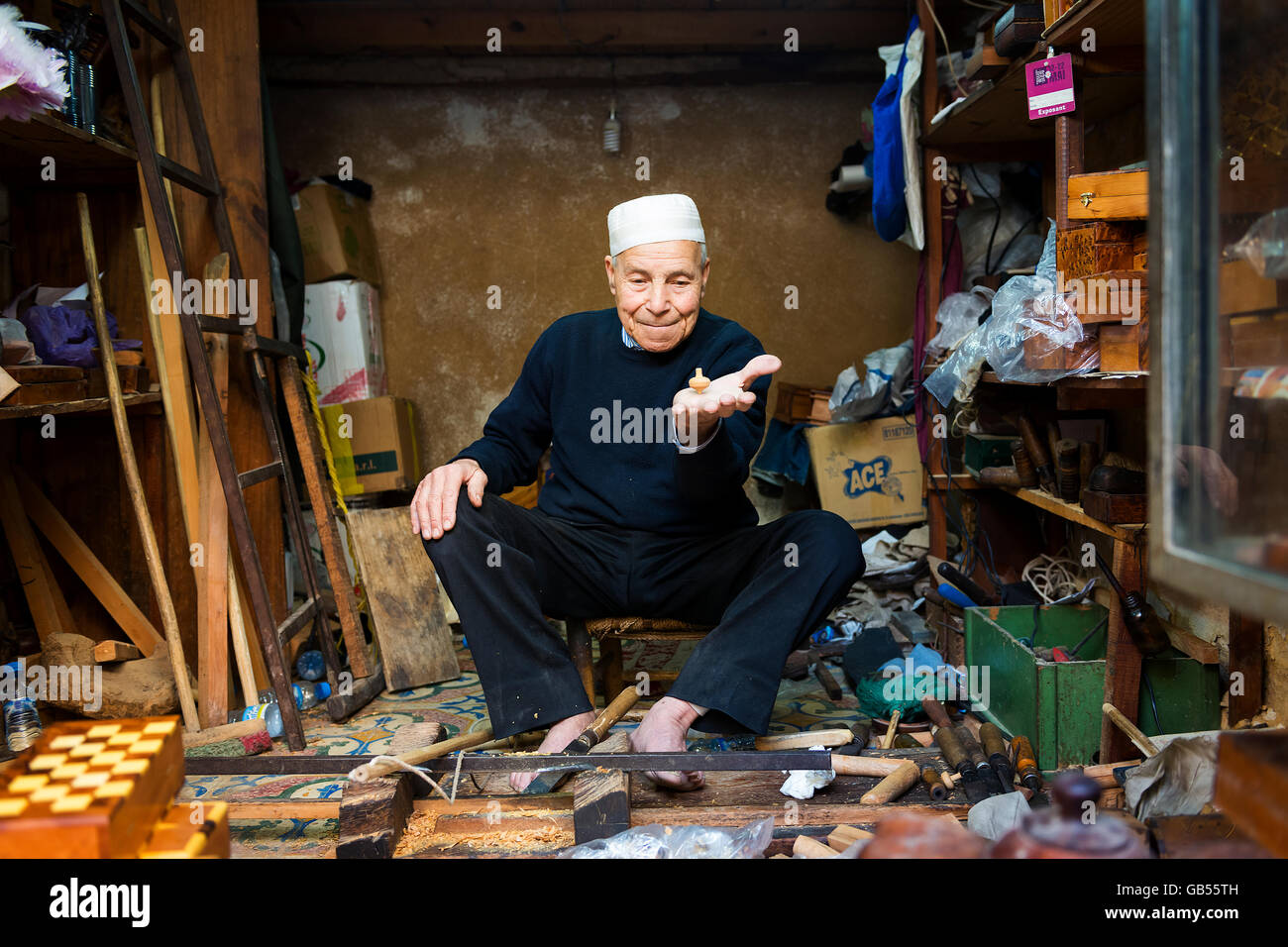 Fez, Morocco - April 11, 2016: An artisan showing a spinning top in his shop in the Fez Medina. - Stock Image