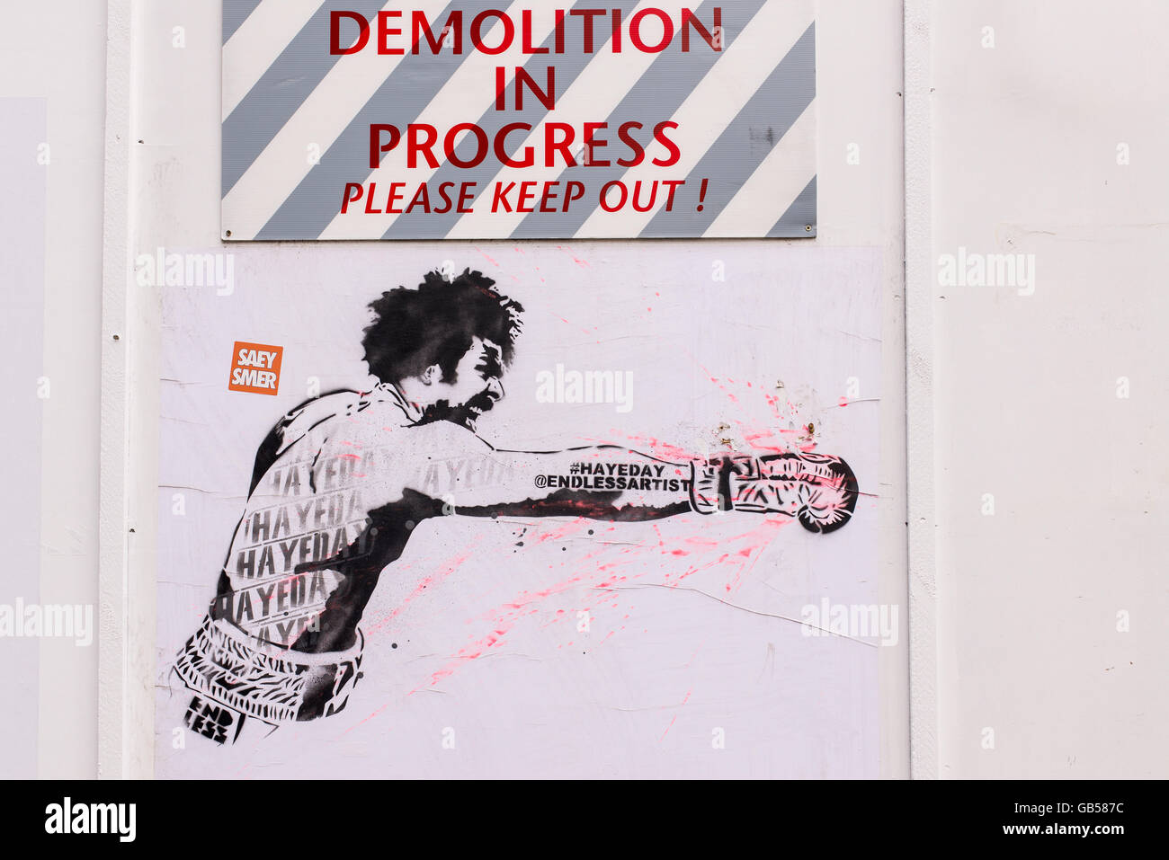 Graffiti in a construction site with boxer David Haye punching with an horizontal fist below a poster saying Demolition - Stock Image