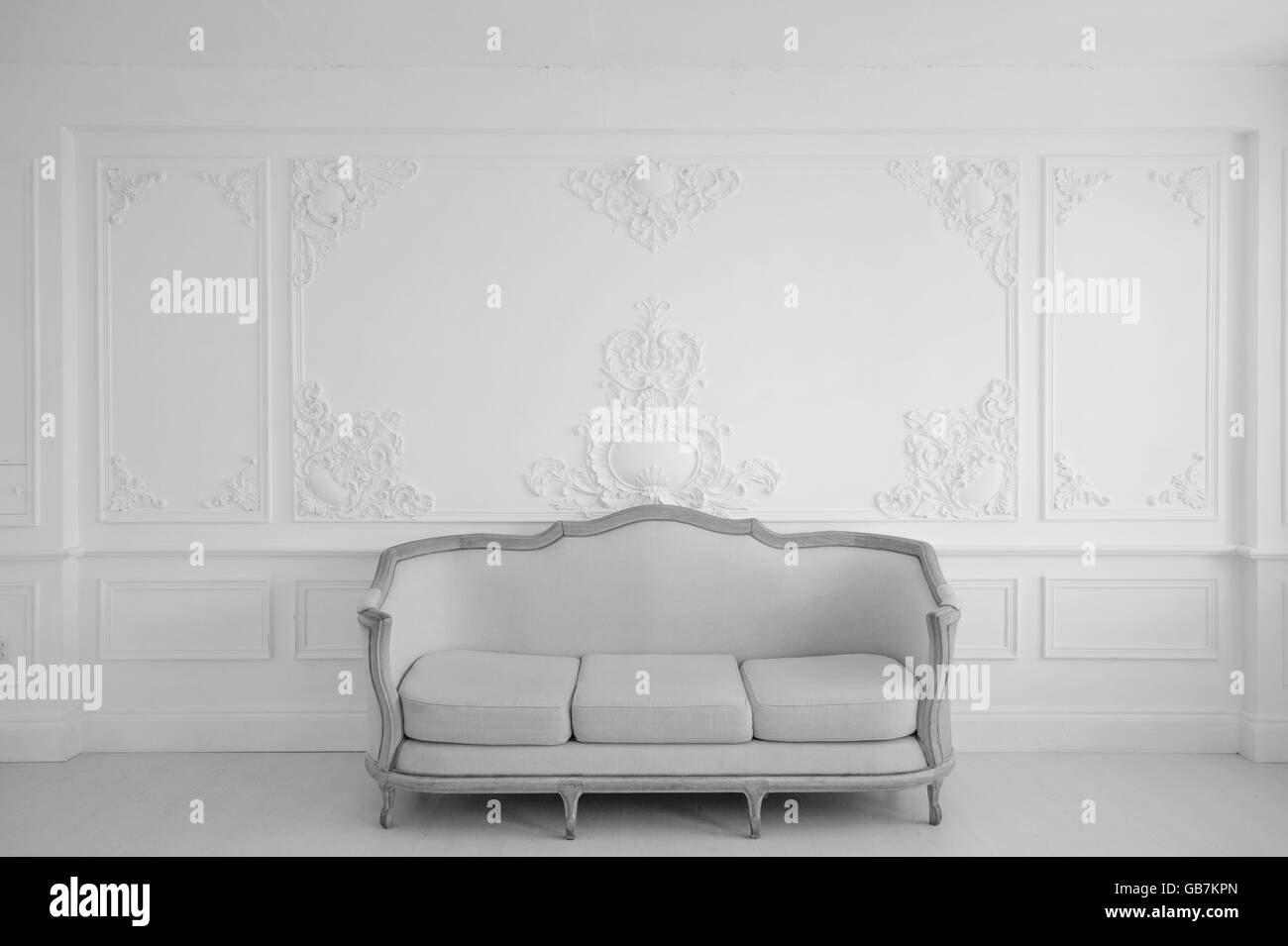 Living room with antique stylish light sofa on luxury white wall ...