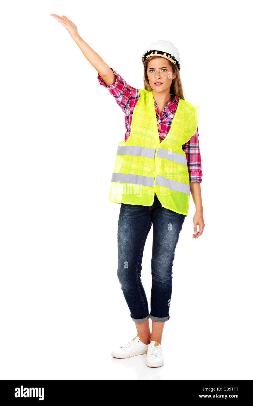 Smiling female builder in vest - Stock Image