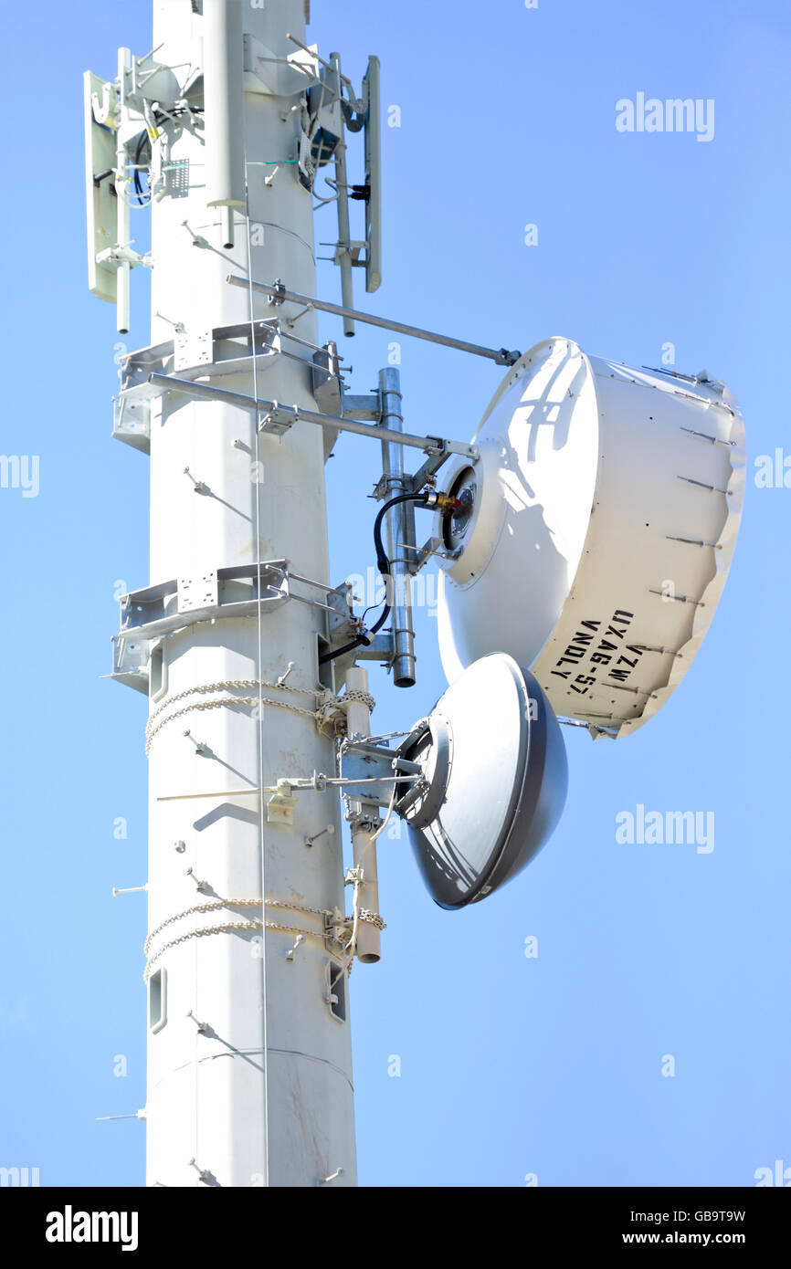 Microwave relay units / dishes on a cell tower to send and receive radio mobile / cellular telephone communications - Stock Image