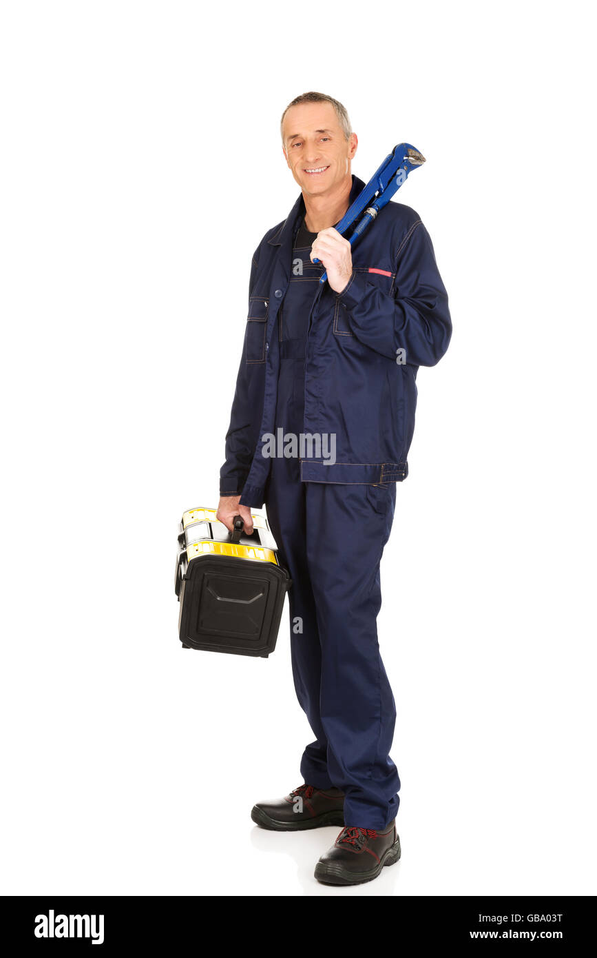 Mature worker with tools bag and wrench - Stock Image