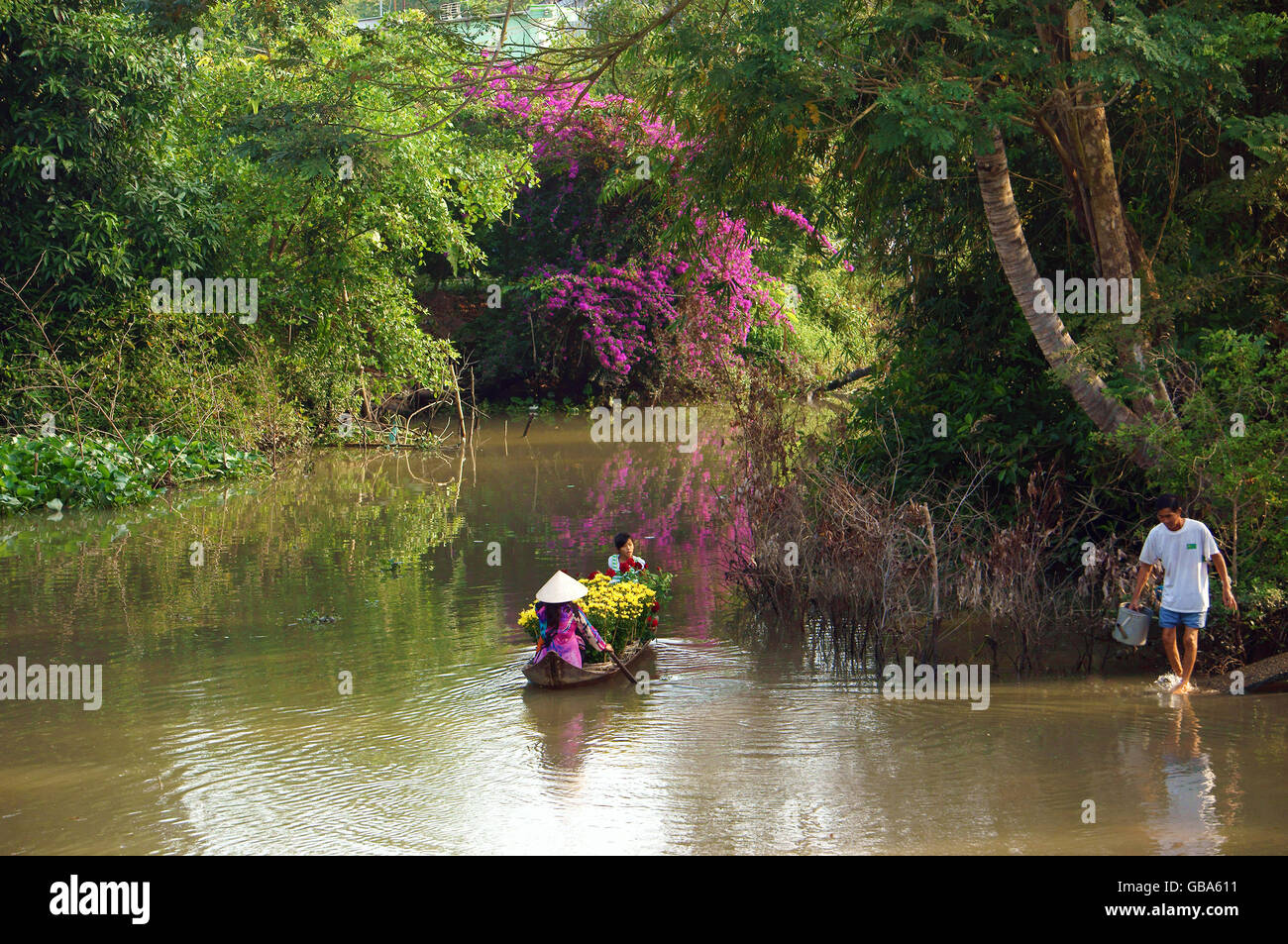 Spring come, women and children rowing the rowboat on river to carry beautiful flower  forTet - Stock Image