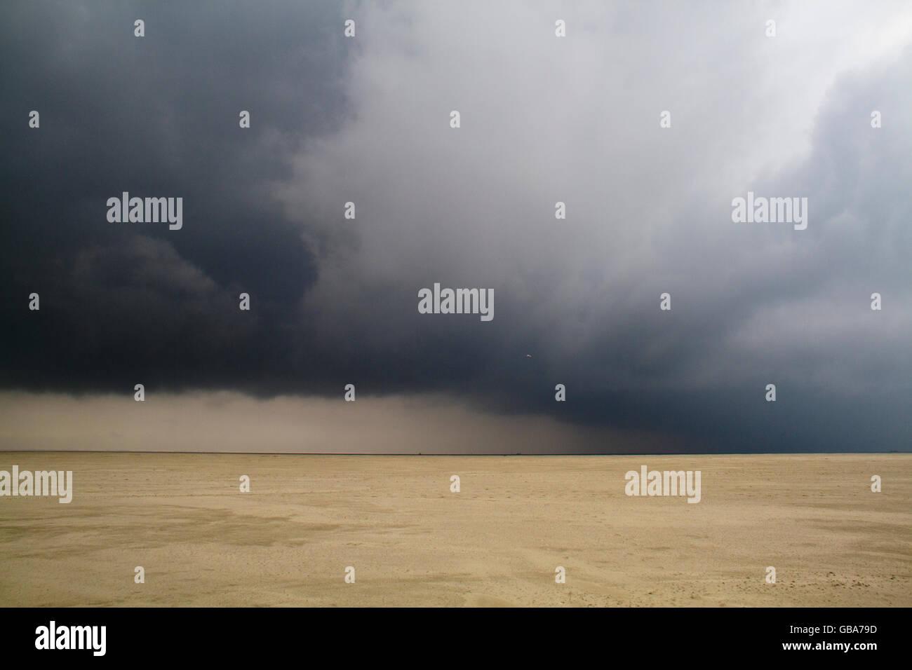Dark, ominous clouds above a vast beach - Stock Image