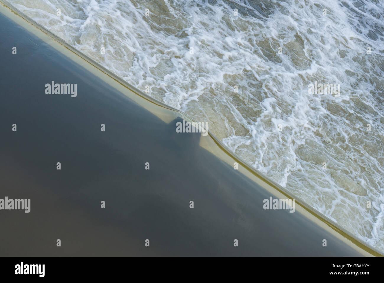 Diagonal water edge of an stream weir - Stock Image