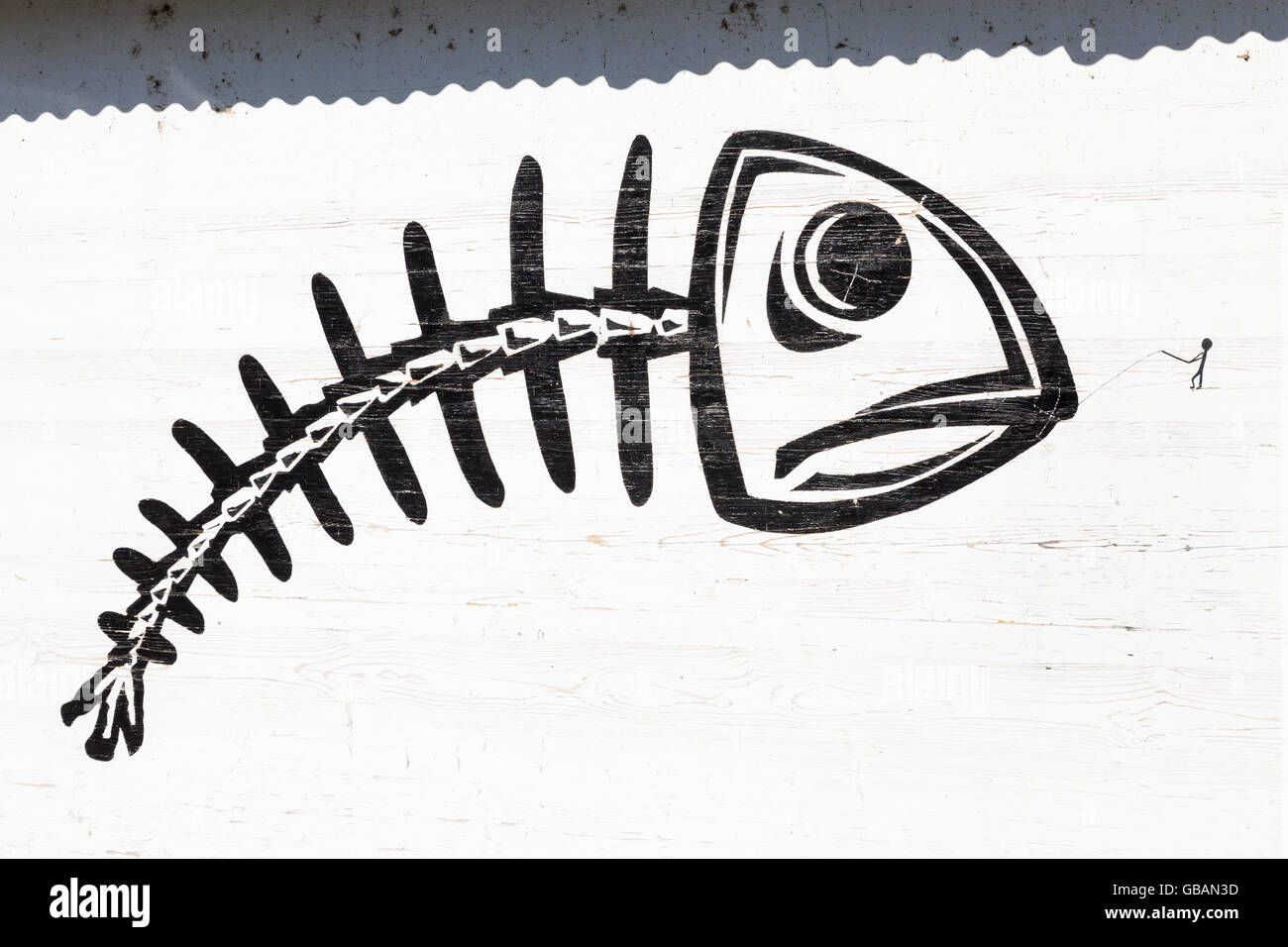 Graffito of a big black skeletal fish on a white wall being caught by a tiny stick figure - Stock Image