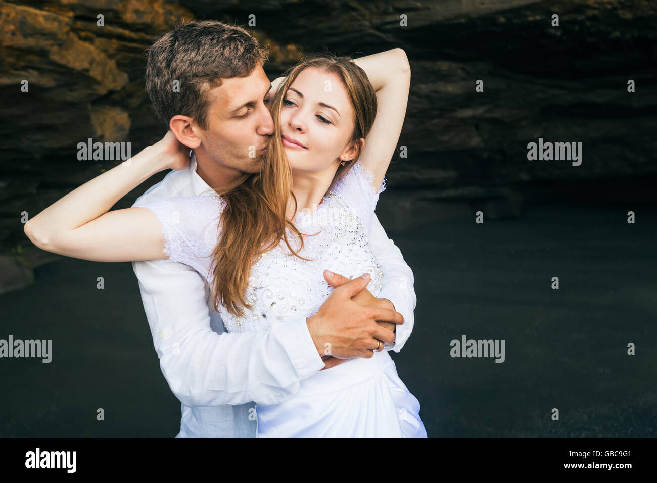 Happy family on honeymoon holiday - just married young man and woman hug with smile on black sand beach with rock Stock Photo