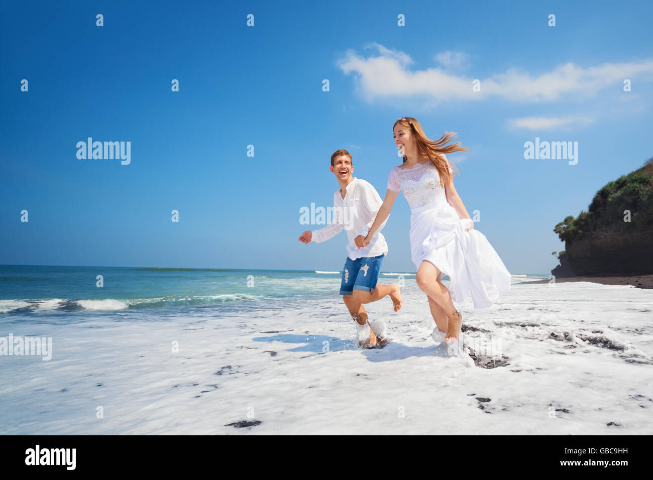Happy newlywed family on honeymoon holiday - just married loving couple run with fun by black sand beach along sea - Stock Image