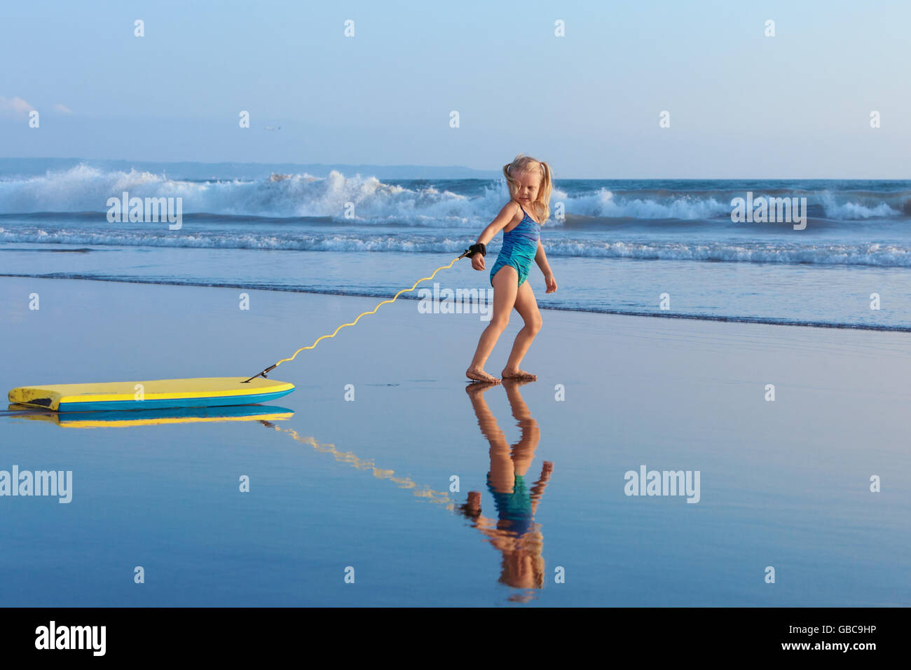 Little baby girl - young surfer with bodyboard has fun on sea beach. Family lifestyle, people water sport activity, - Stock Image