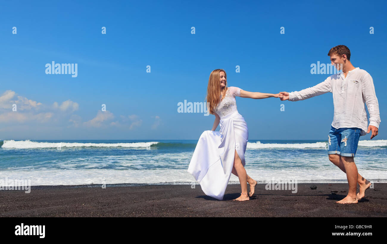 Happy family on honeymoon holiday - just married young man and woman run with fun by black sand beach along sea - Stock Image