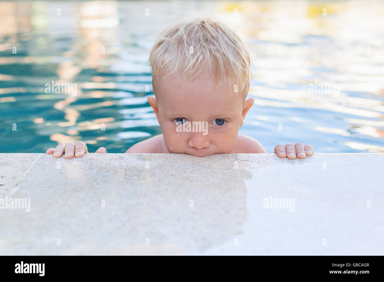 Child learn to swim - funny face of little baby boy in pool. Active healthy lifestyle, water sport, children physical - Stock Image