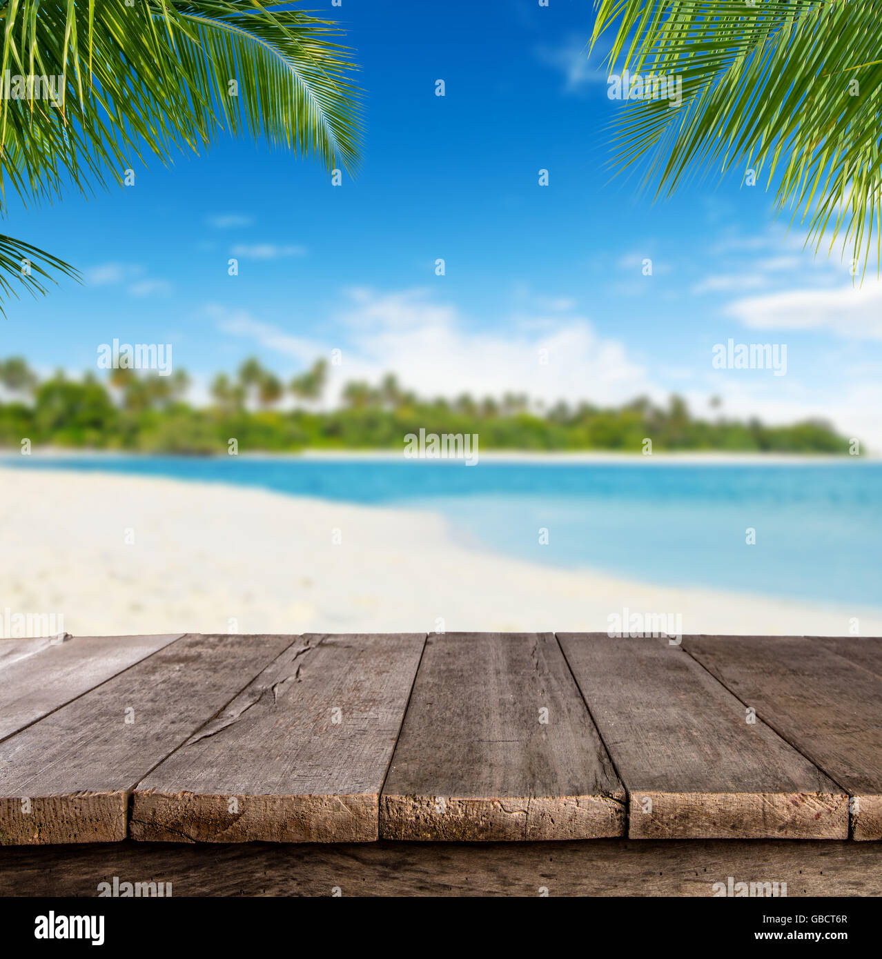 Empty wooden planks with blur beach on background, can be used for product placement, palm leaves on foreground - Stock Image