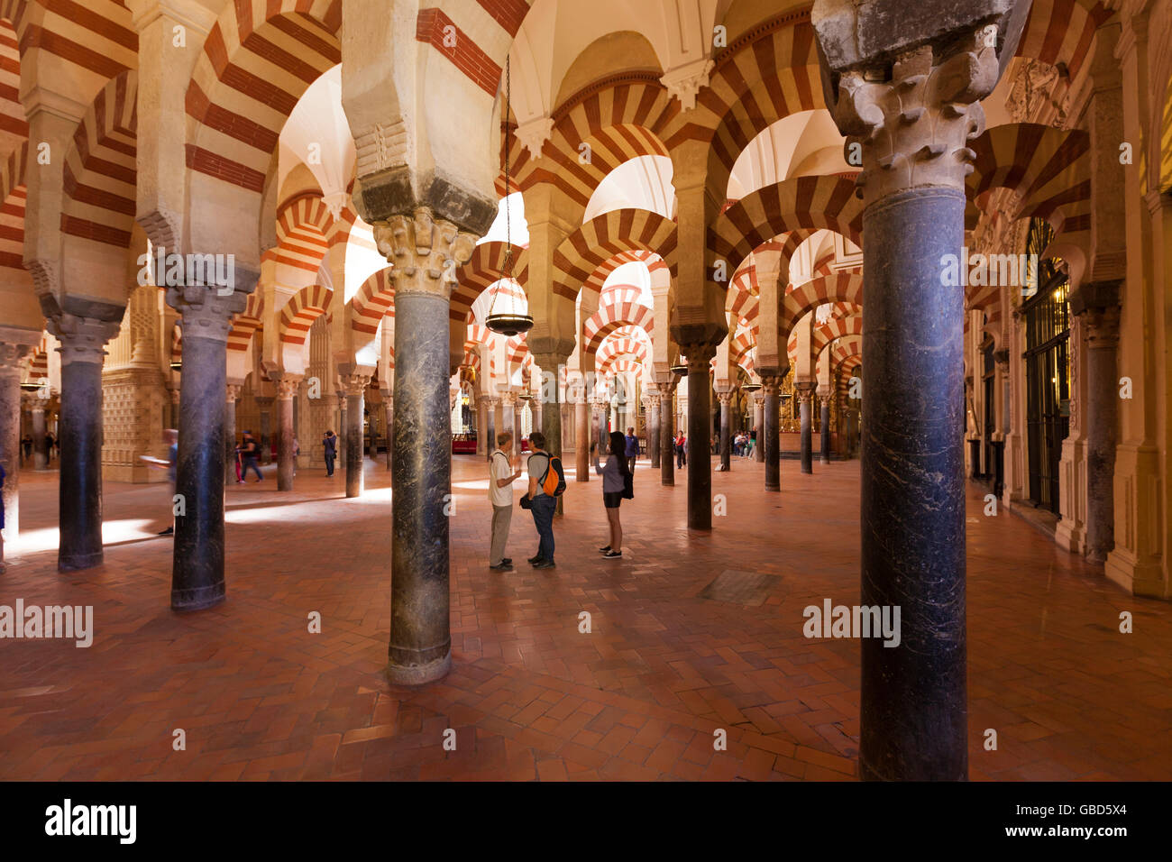 Visitors below the arches inside the Mosque-Cathedral of Córdoba, Spain Stock Photo