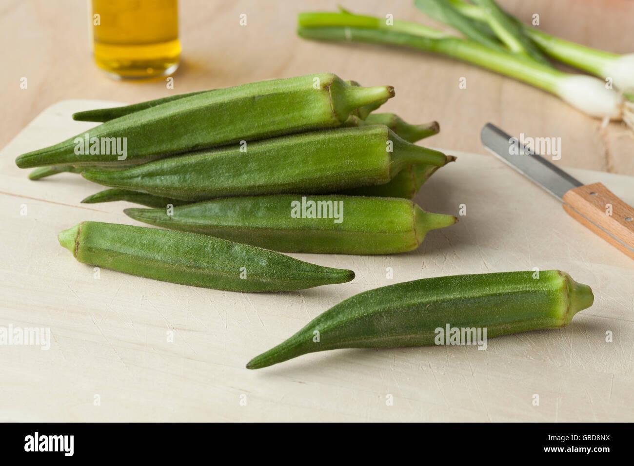 Fresh green okra on a wooden cutting board - Stock Image