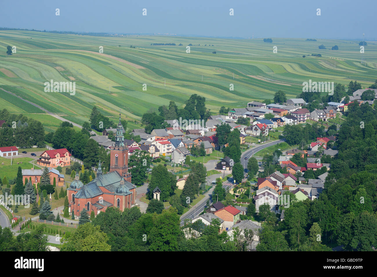 VILLAGE SURROUNDED BY GREEN NARROW FIELDS (aerial view). Suloszowa, Poland. - Stock Image