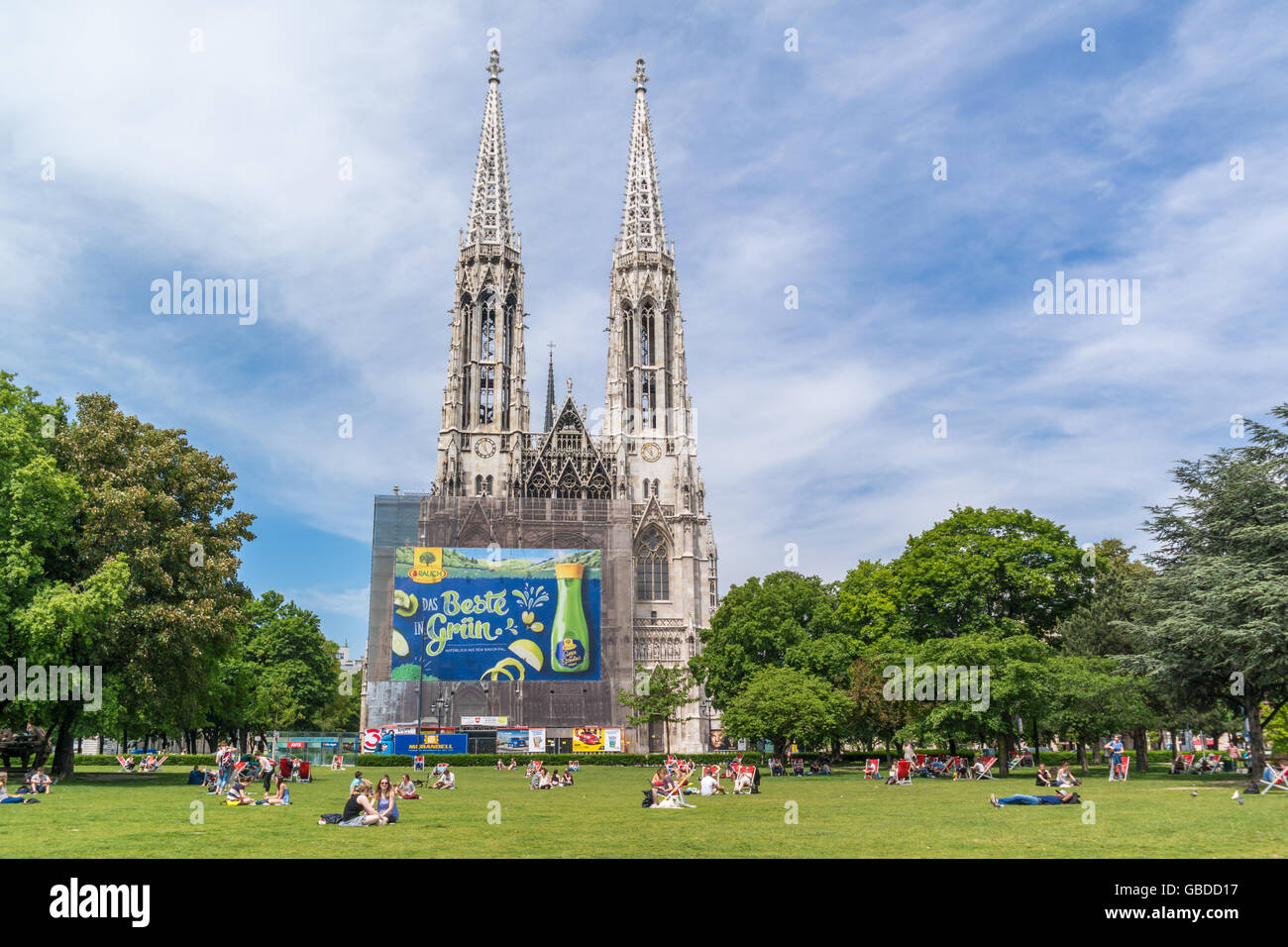 People relaxing in Sigmund Freud Park and Votive Church at Ringstrasse in inner city of Vienna, Austria Stock Photo