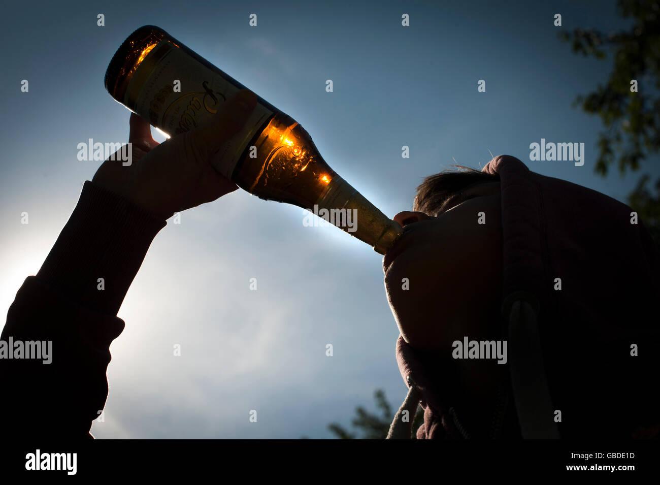 Teenager drinking beer. - Stock Image