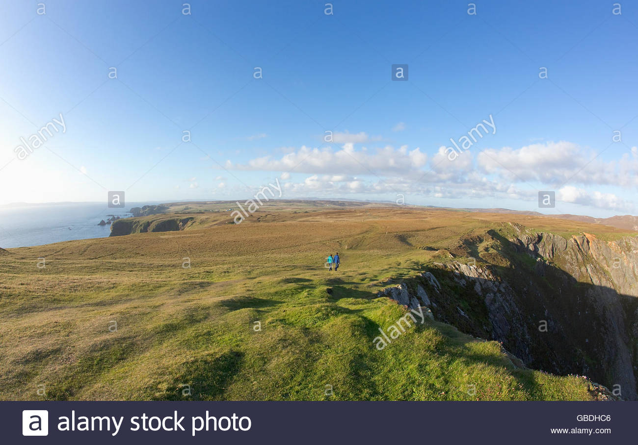A couple walking by the cliff edge at the Mull of Oa on the Isle of Islay, Inner Hebrides, Scotland. - Stock Image