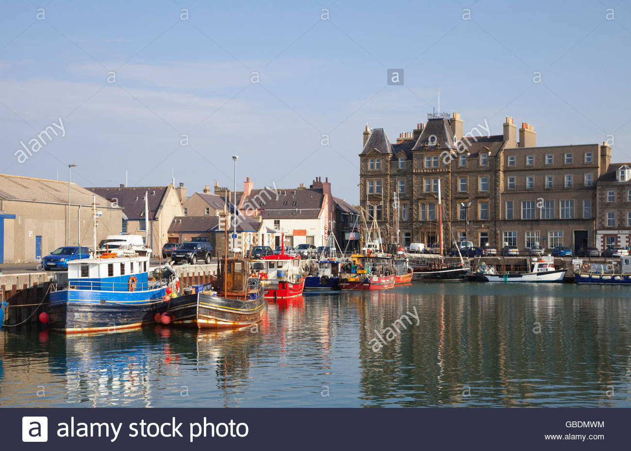 Fishing Boats moored in the harbour at Kirkwall with the Kirkwall Hotel visible, Mainland, Orkney, Scotland. - Stock Image