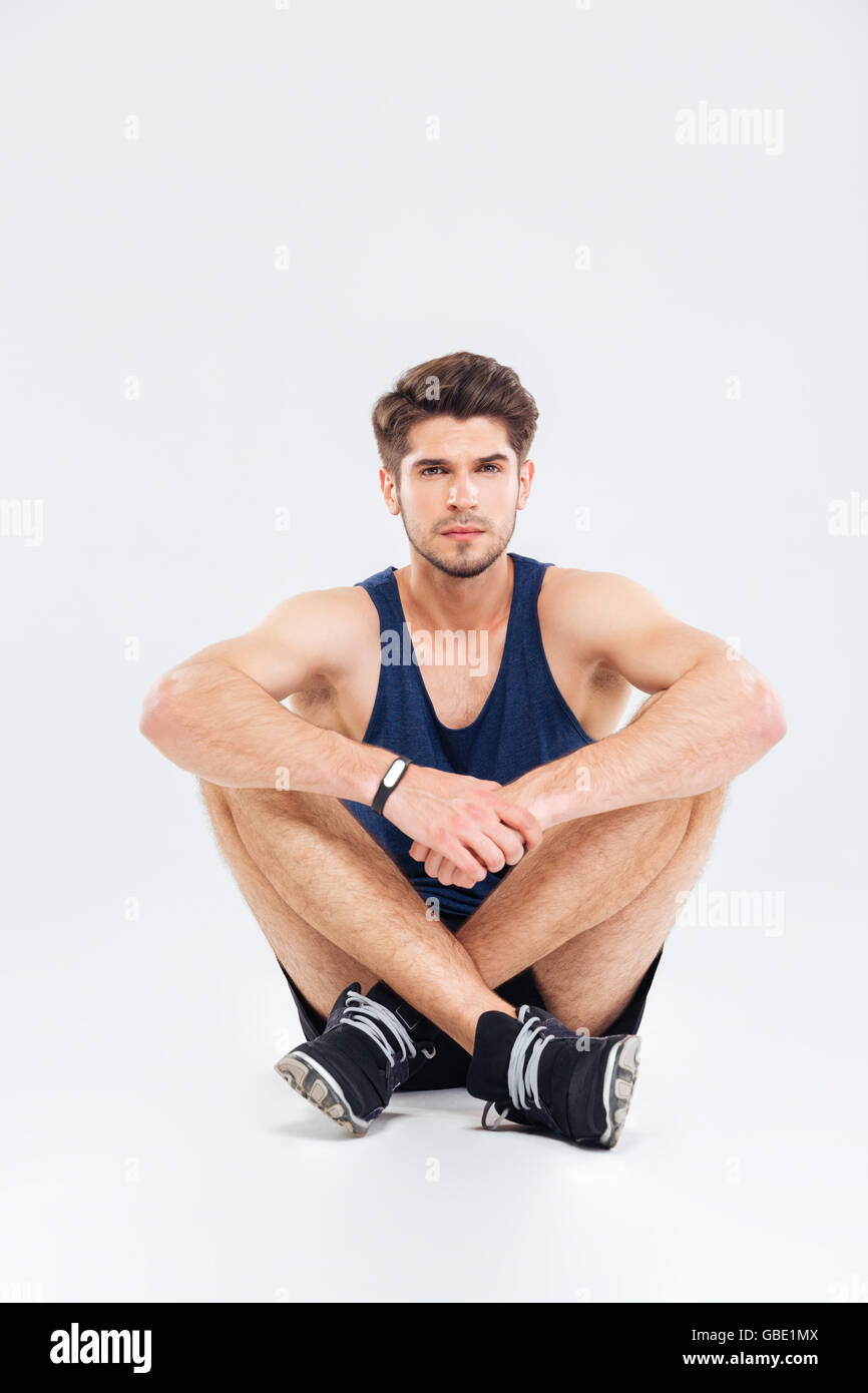 Portrait of confident young sportsman sitting with legs crossed over white background - Stock Image
