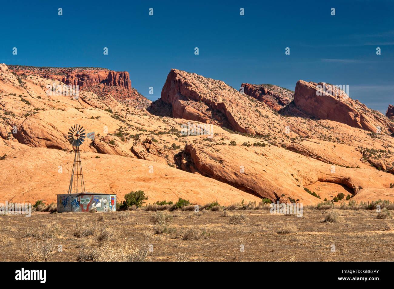 Windmill and water tank, Skeleton Mesa sandstone slickrock behind, Navajo Indian Reservation, near Kayenta, Arizona, - Stock Image