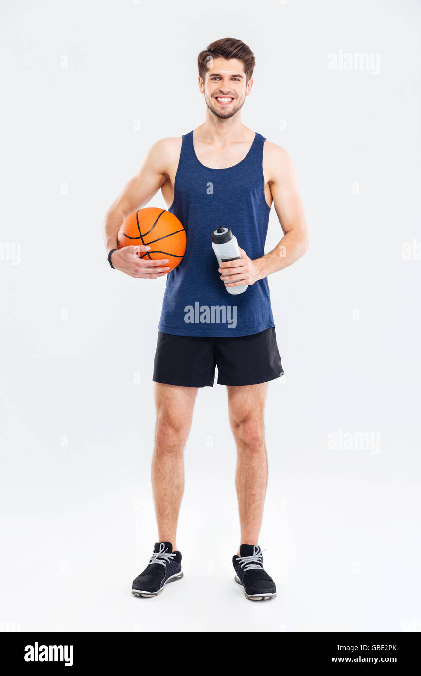 Smiling young handsome sportsman holding basket ball and water bottle isolated on a gray background - Stock Image