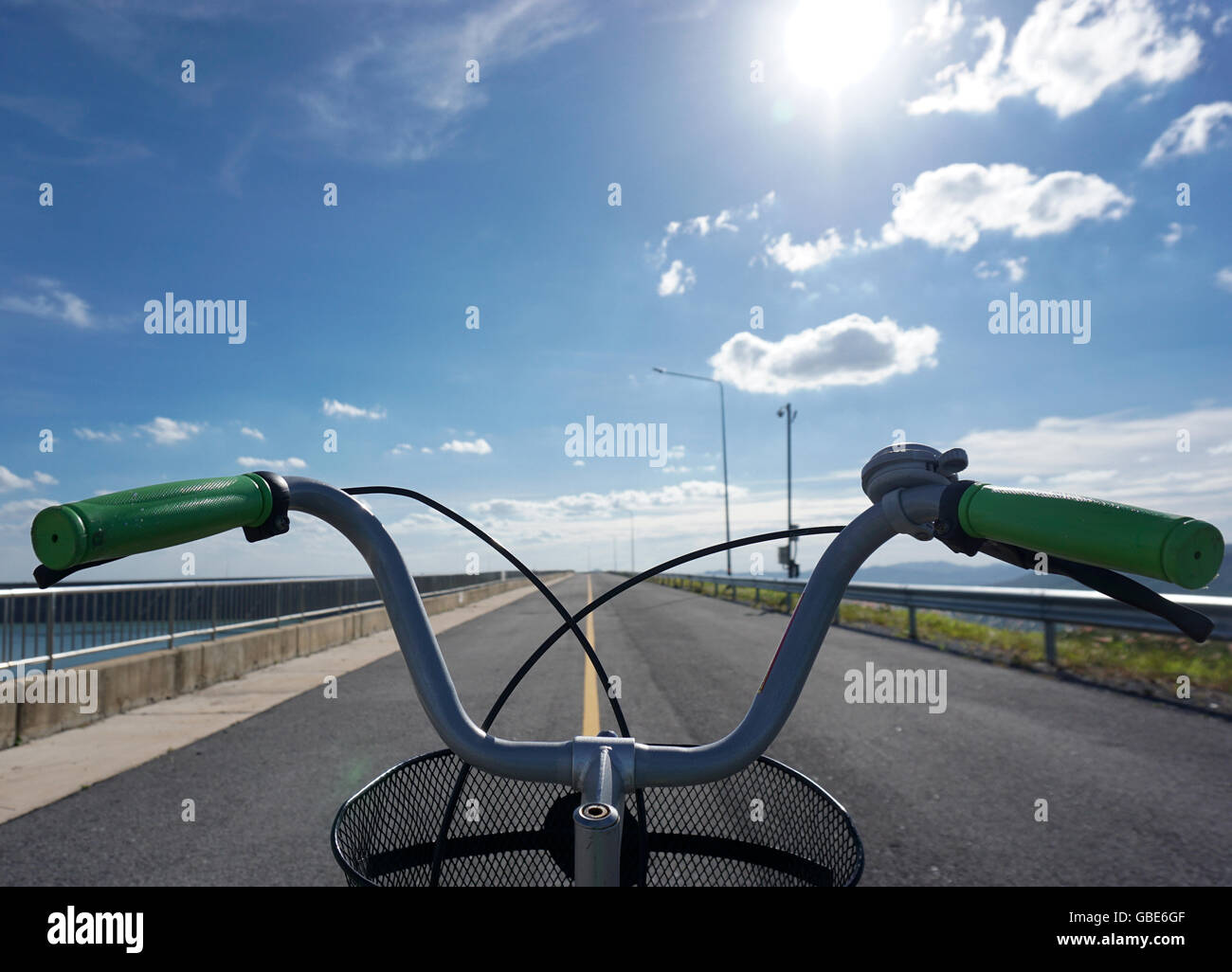 bicycle only handlebars straight ahead direction with blue sky background - Stock Image