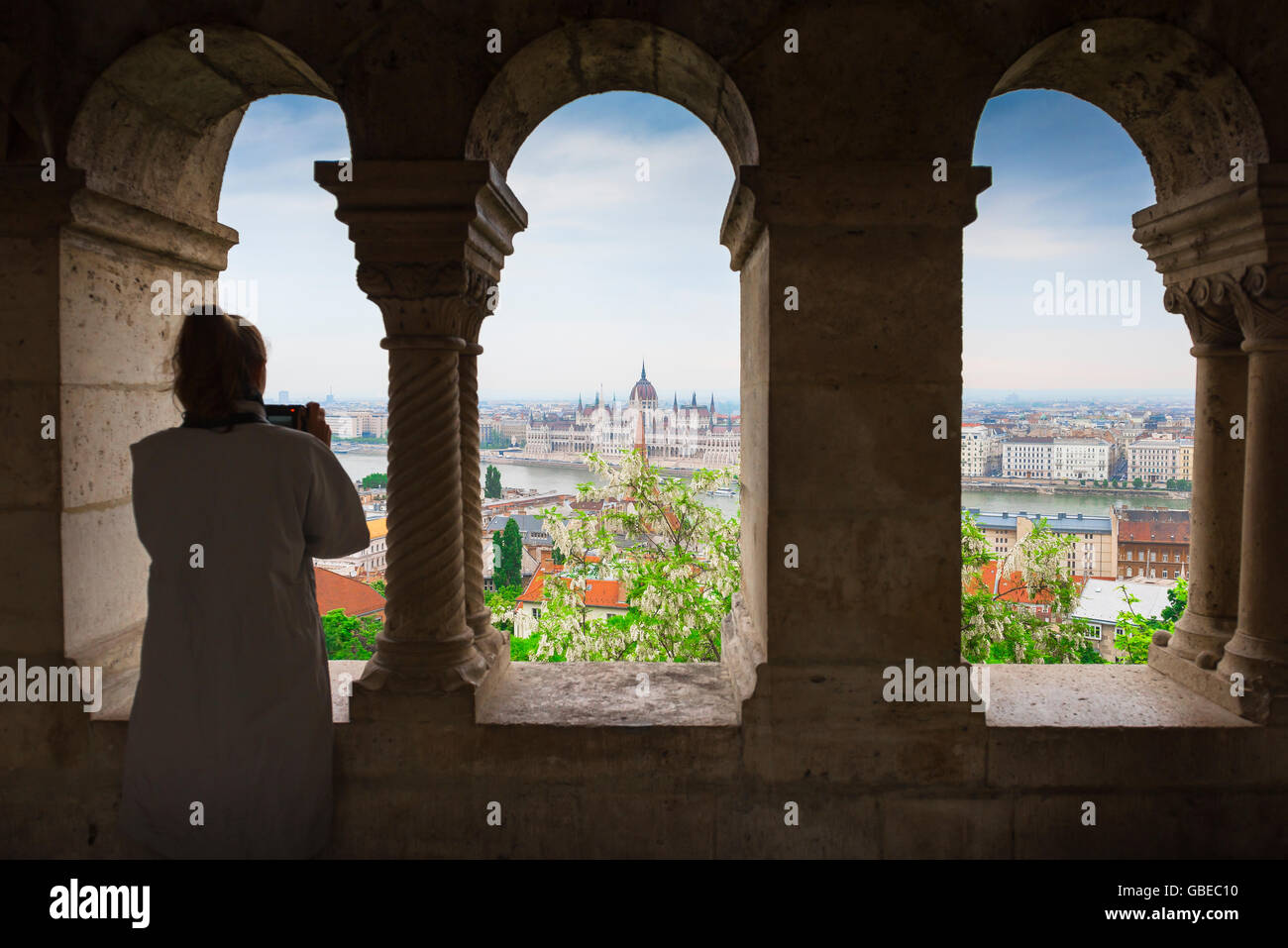 Woman taking photo, a tourist standing in a cloister in the Fishermens Bastion in Budapest photographs the Parliament - Stock Image