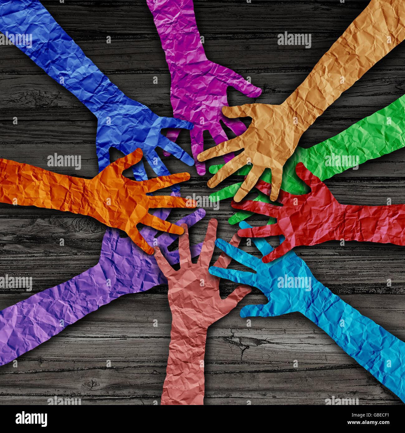 Diverse people team joining hands together as a partnership teamwork concept as a group of paper cut out hands as - Stock Image