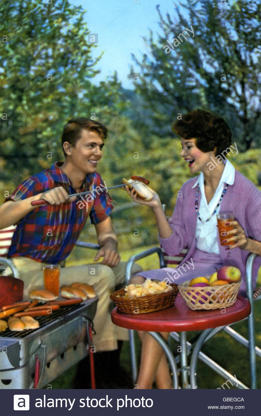 festivity, barbecue, couple having barbecue in garden, coloured postcard, 1960s, Additional-Rights-Clearences-NA - Stock Image