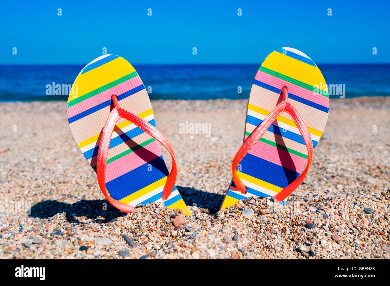 closeup of a pair of colorful striped flip-flops with pink straps stuck on the sand of a beach - Stock Image