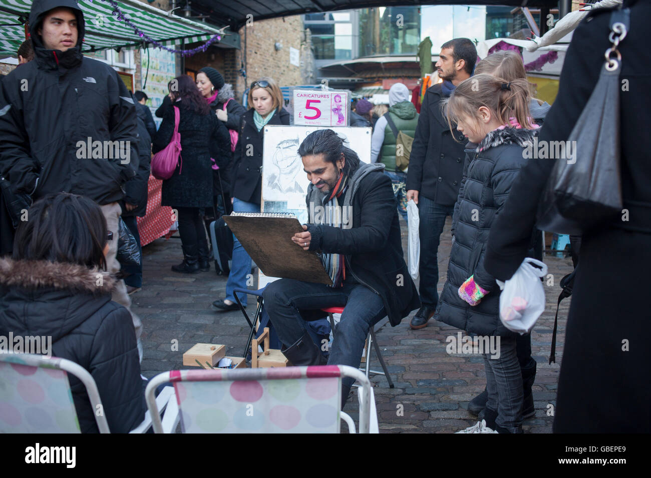 Caricaturist working in Camden's The Stables Market - Stock Image