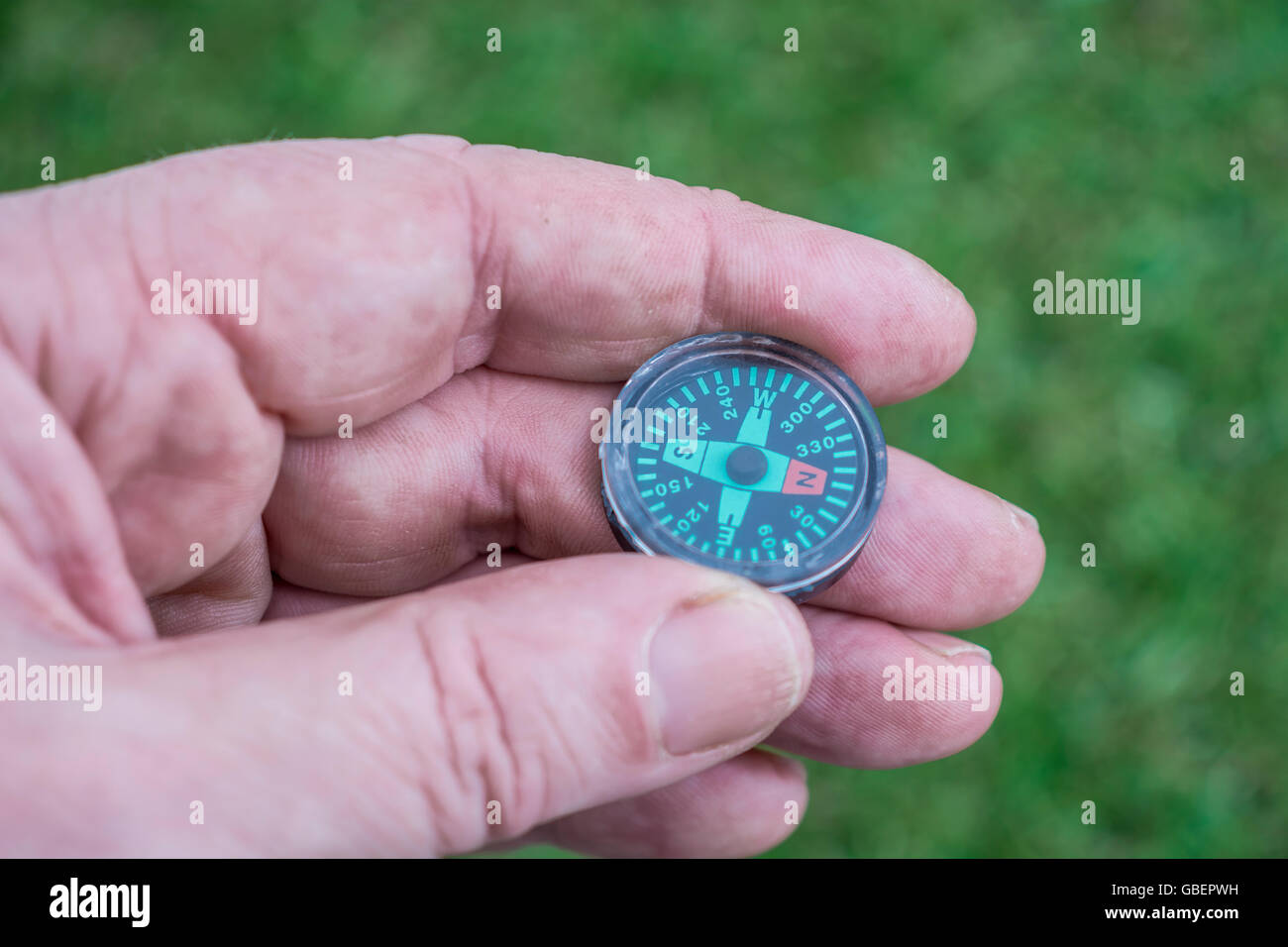 Concept of direction navigation, and knowing where you are going or finding your way, illustrated by a hand-held - Stock Image