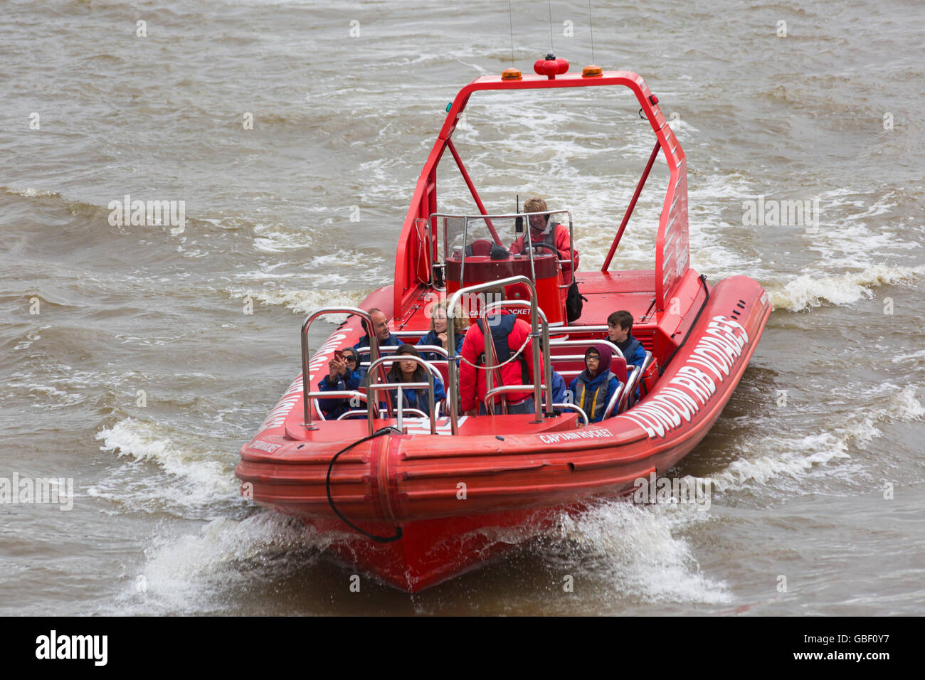 Tourists experiencing ride on Captain Rocket London Rib Voyages on River Thames, London in July - Stock Image