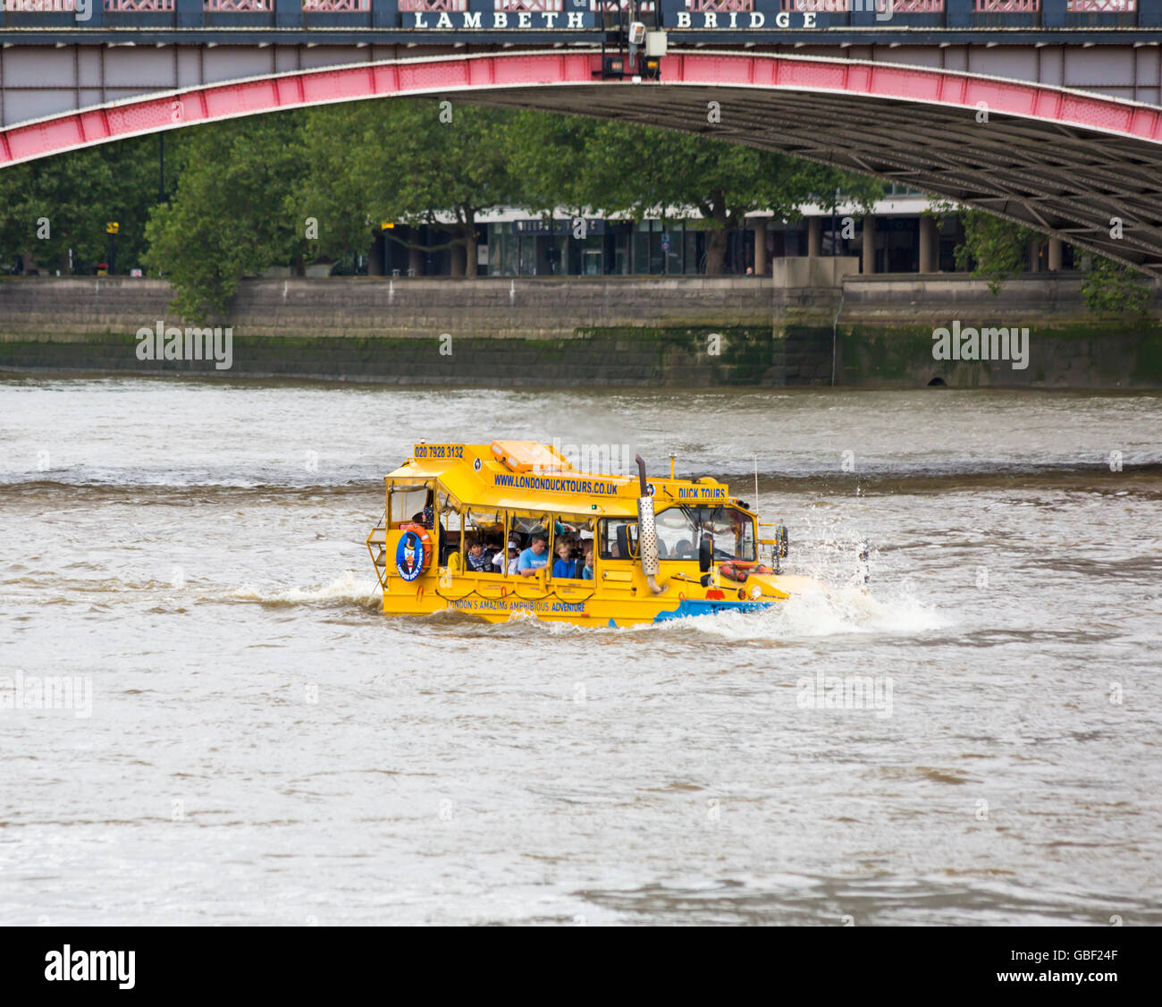 London Duck Tours amphibious vehicle boat going along River Thames under Lambeth Bridge, London in July - Stock Image