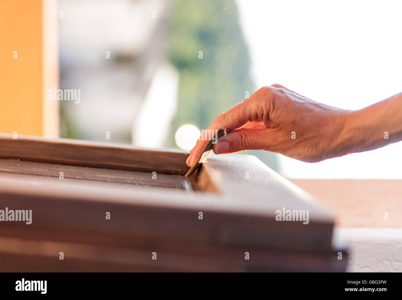 Hands of a woman with sandpaper doing DIY work on wooden fixtures - Stock Image